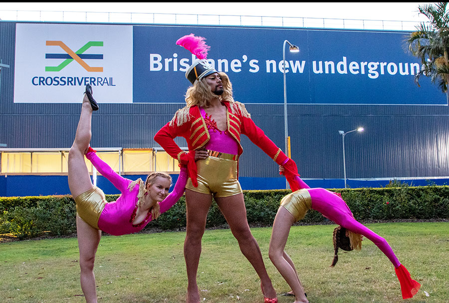 three dancers in colourful costumes in front of the Roma Street acoustic shed